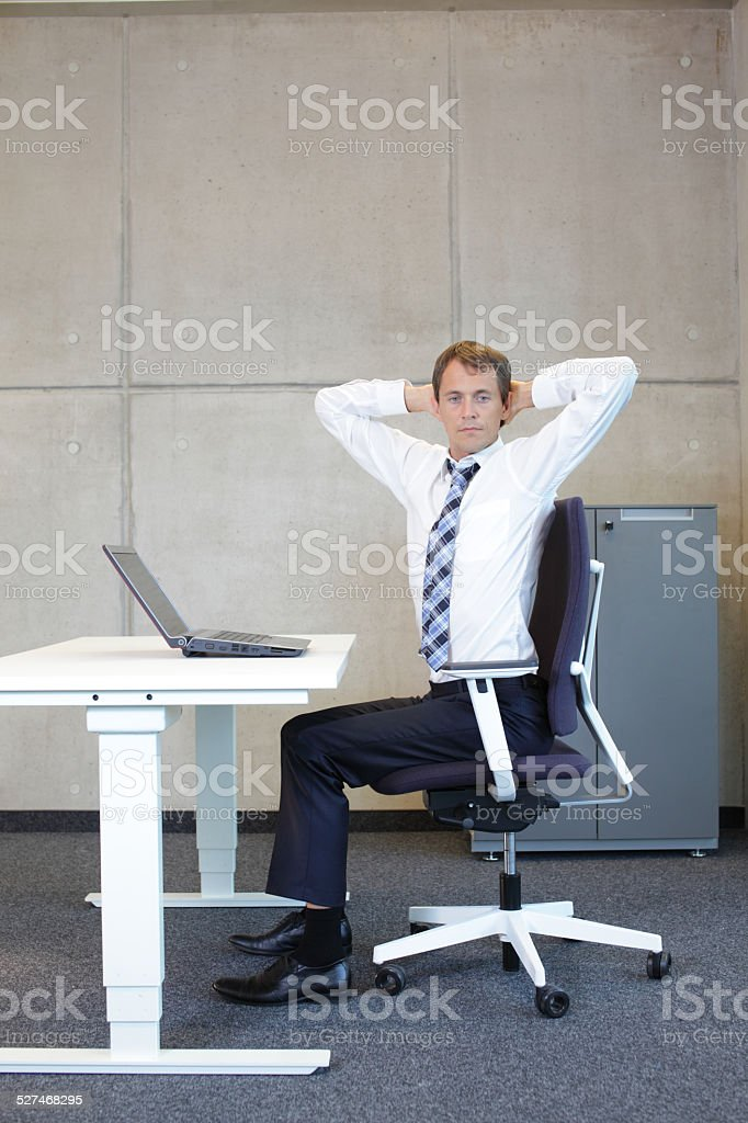 exercises in office. business man arm-neck stretching stock photo