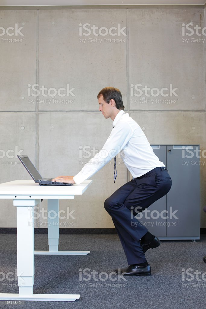 exercises in office. business man practicing yoga stock photo