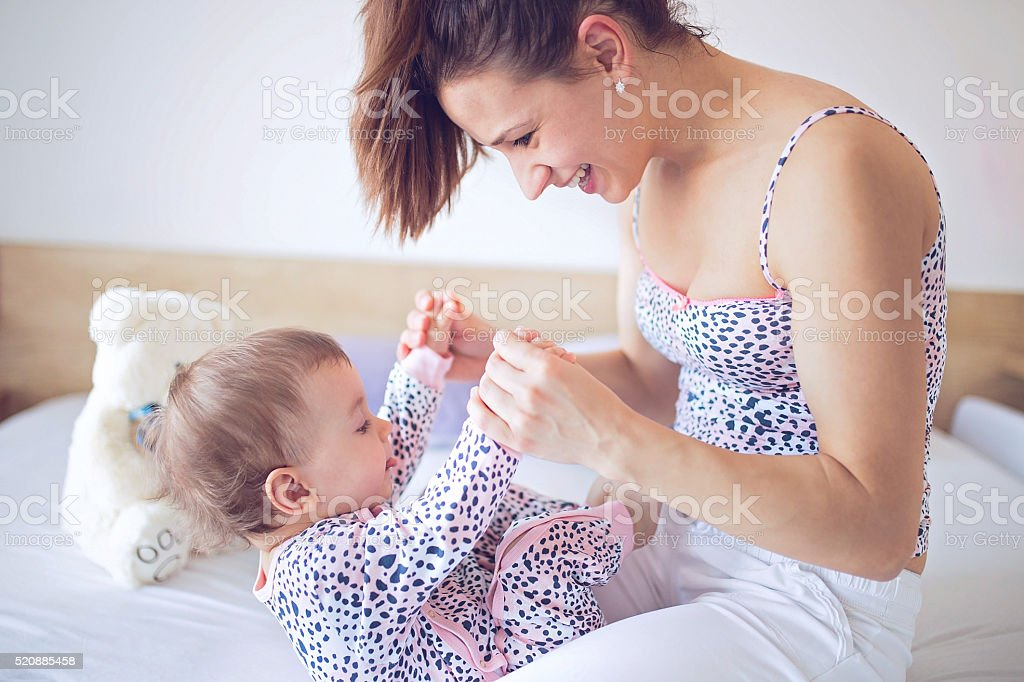 Exercises on bed, mom adn baby stock photo