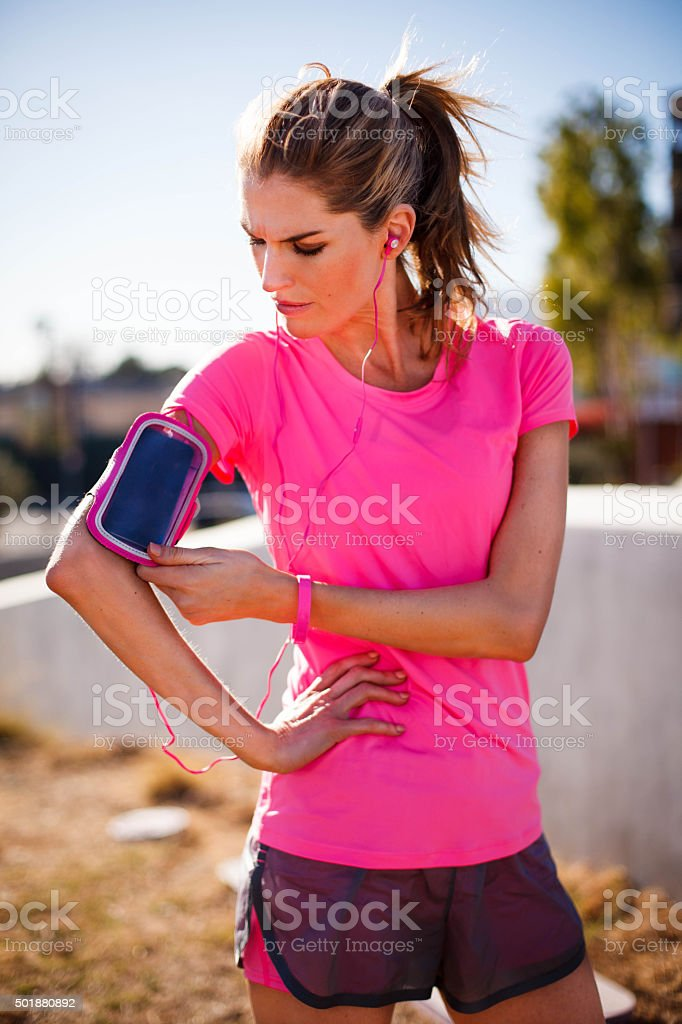 Exercising fitness woman configures her mp3 music player cellphone stock photo