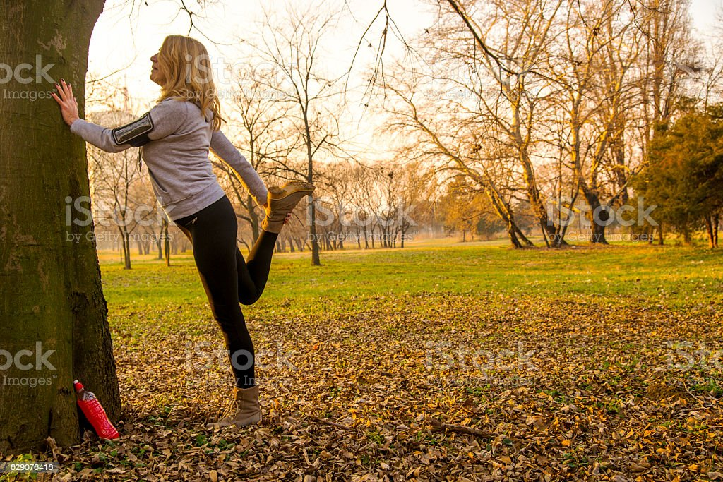 Exercising mature woman outdoors in autumn park during the day stock photo