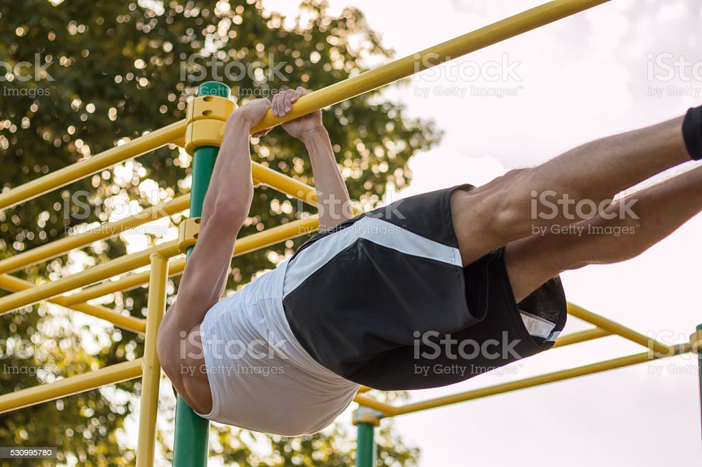 exercising on horizontal bar outdoors stock photo