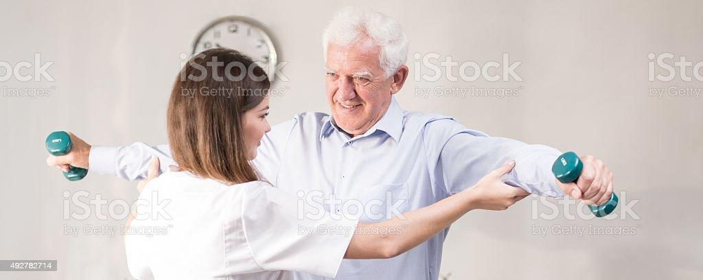 Exercising with dumbbells during rehabilitation stock photo