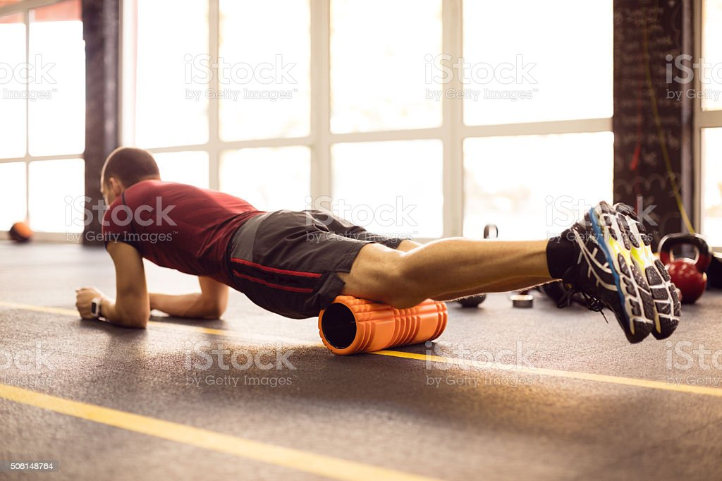 Exercising with foam roller in the gym stock photo