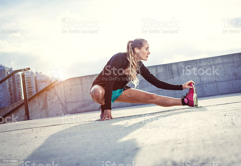Exercising young woman outdoors stock photo