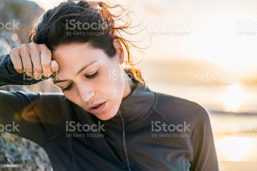 Exhausted athlete is wiping forehead at beach stock photo