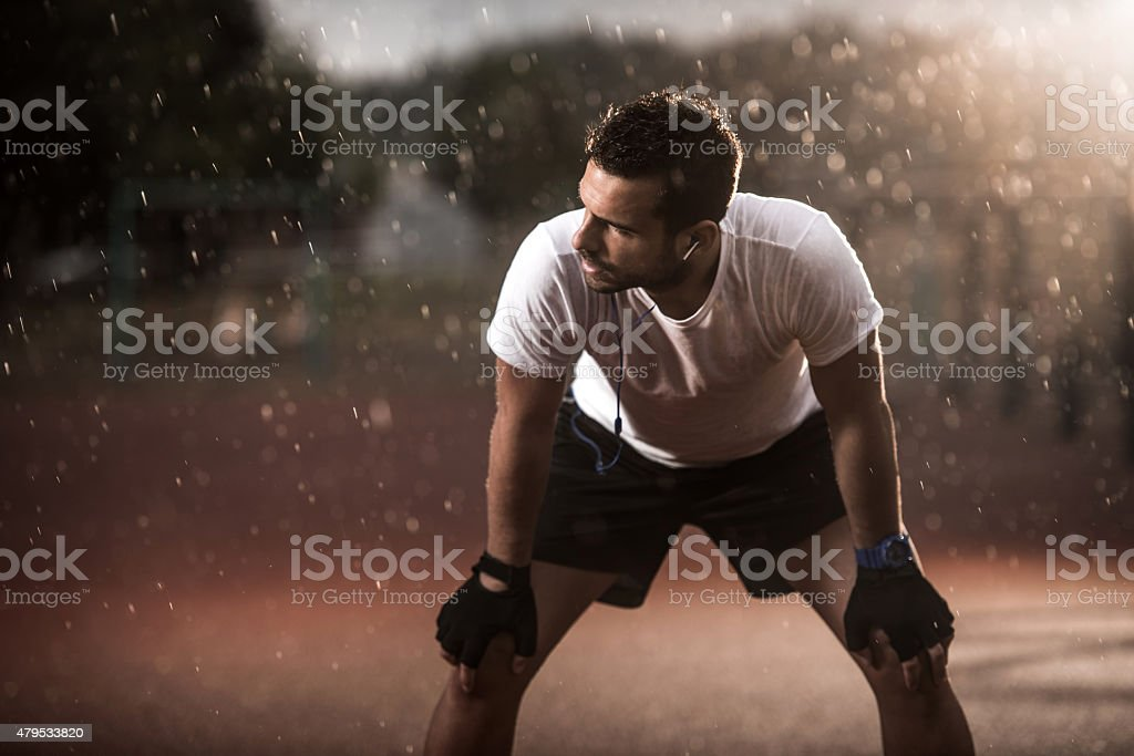 Exhausted athlete taking a breath after exercising on a rain. stock photo