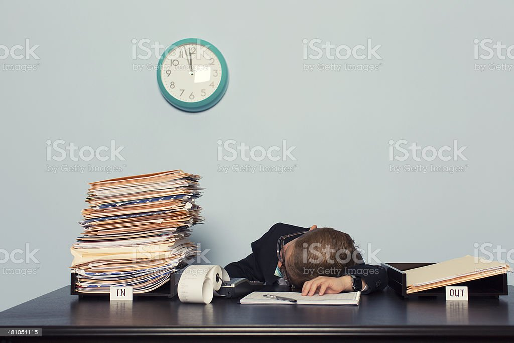 Exhausted Boy Businessman Lays on Office Desk stock photo