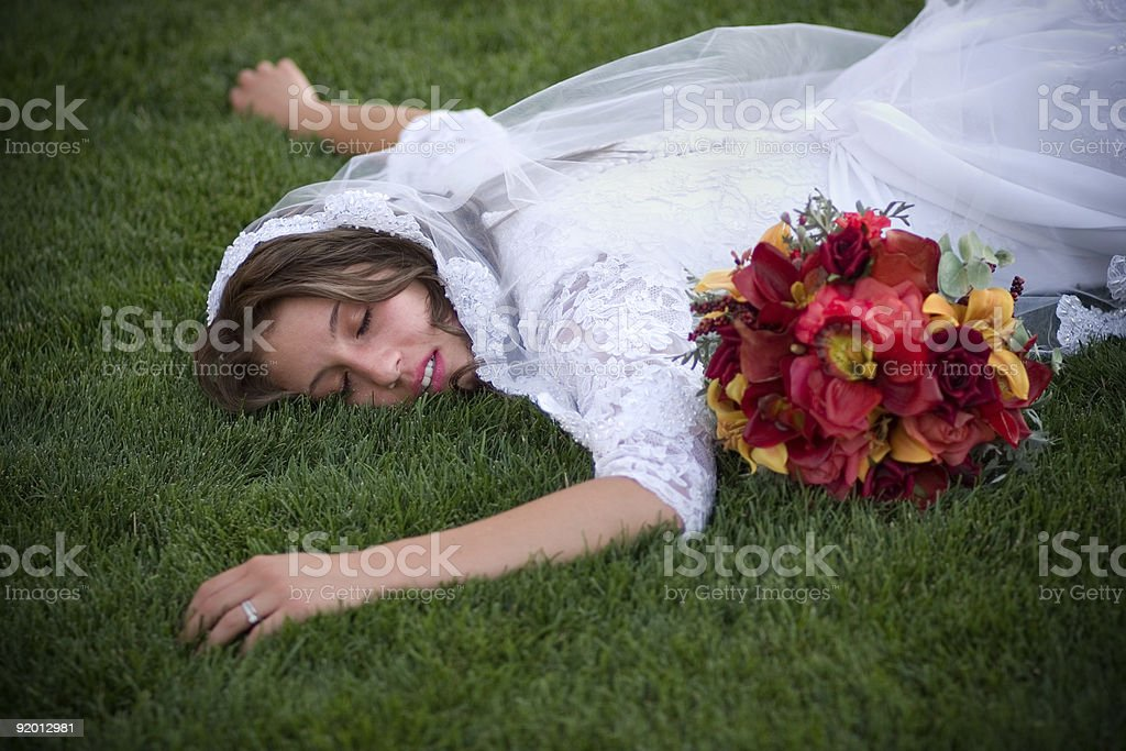 Exhausted Bride with Flower Bouquet Lying Face Down on Grass royalty-free stock photo