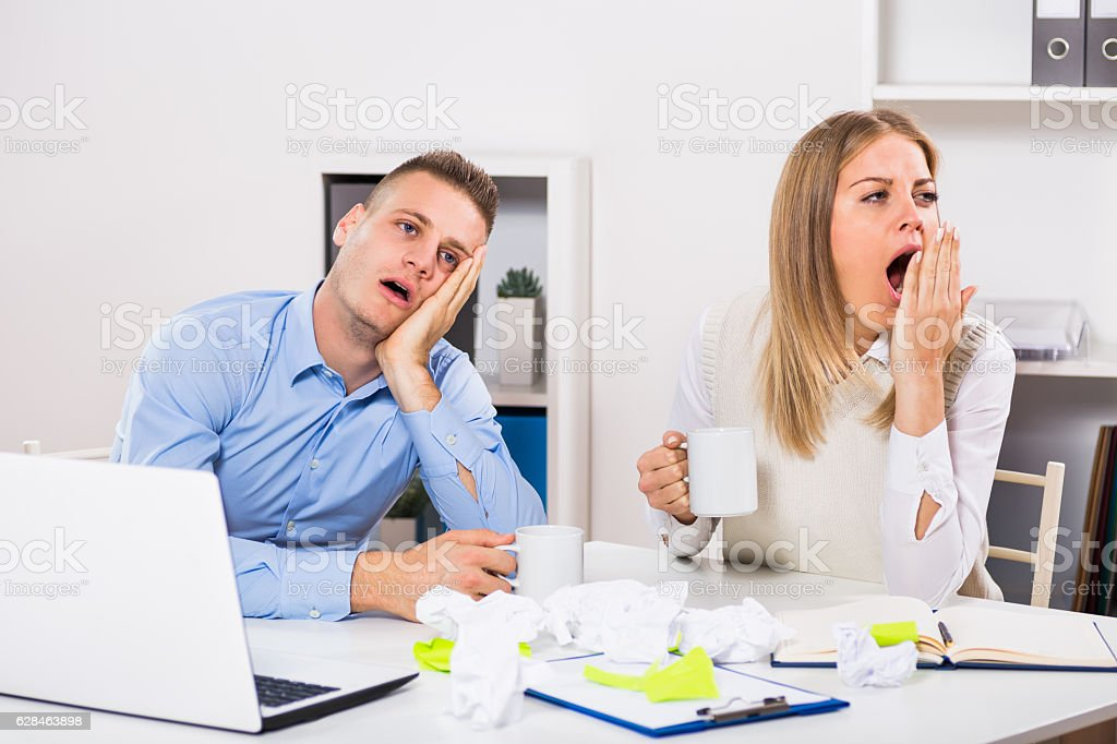 Exhausted businessman and businesswoman drinking coffee stock photo