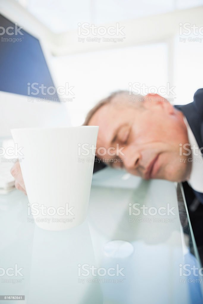 Exhausted businessman asleep at work stock photo