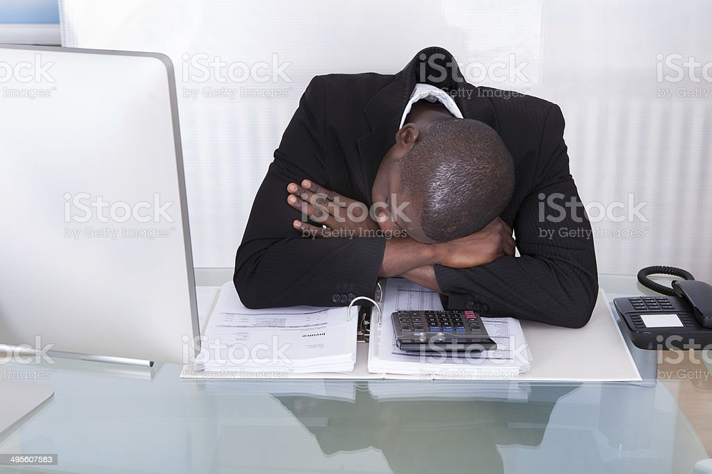 Exhausted Businessman At Desk stock photo