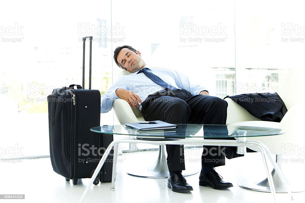 Exhausted businessman at the airport stock photo