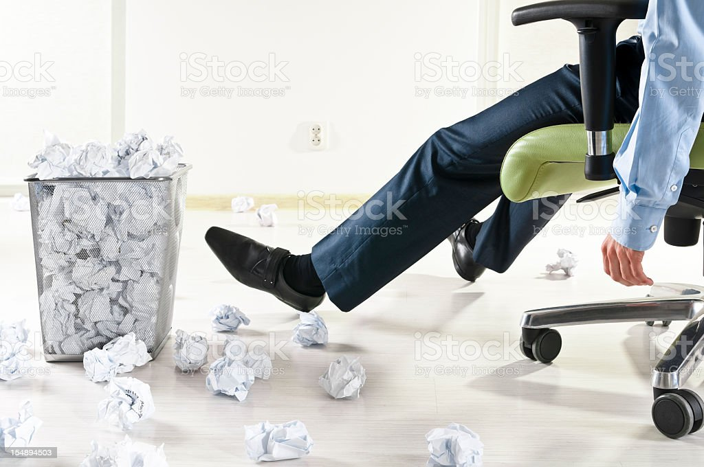 Exhausted businessman at the office, many crumpled paper balls stock photo