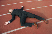 Exhausted Businessman Lying on Sports Track