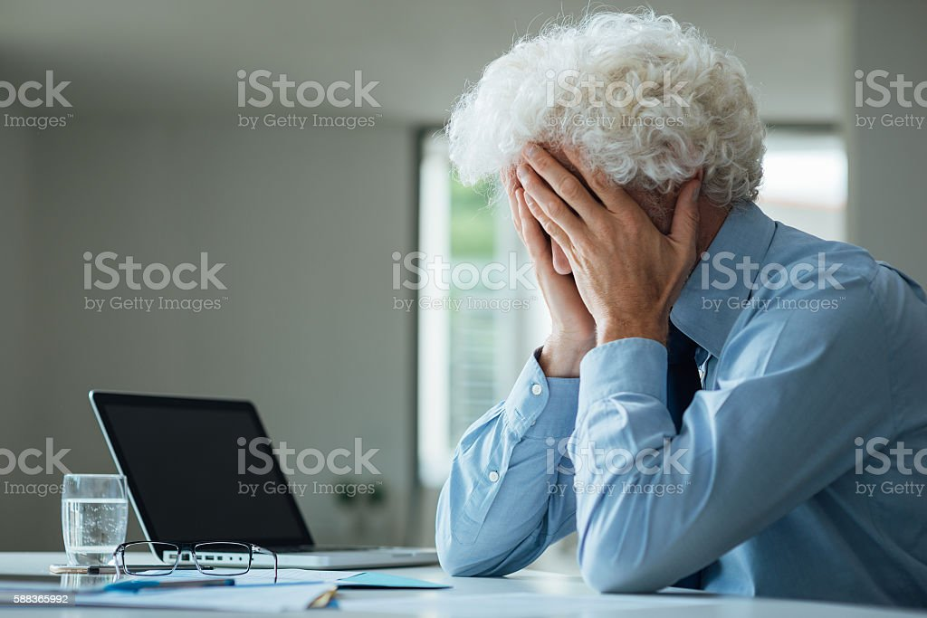 Exhausted businessman with head in hands stock photo