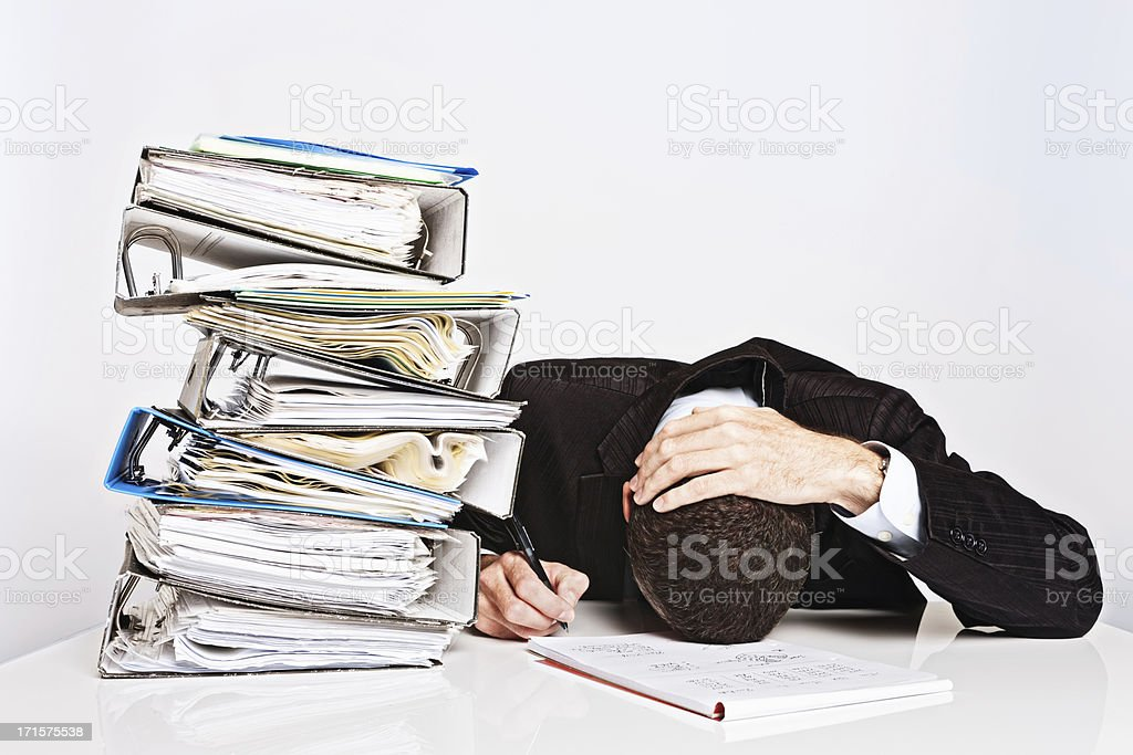 Exhausted businessman with too much work collapses over desk royalty-free stock photo