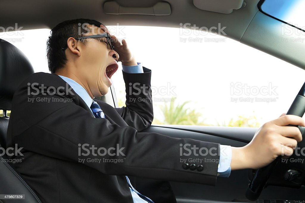 Exhausted driver yawning and driving  car royalty-free stock photo