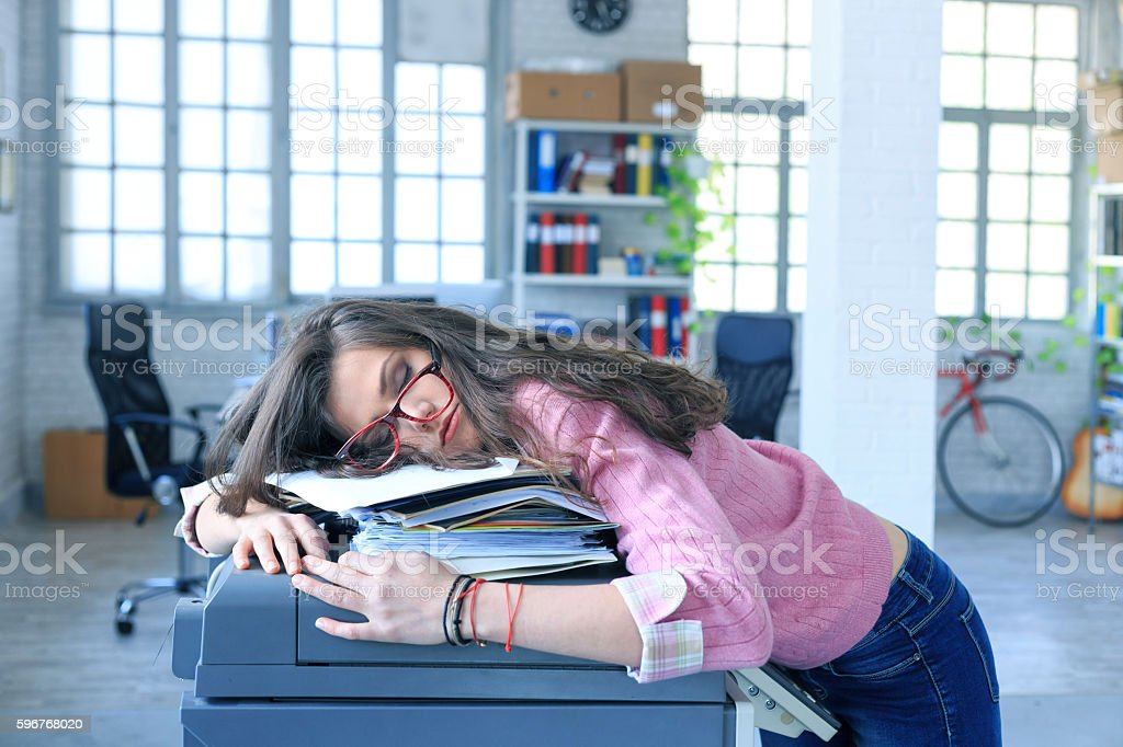 Exhausted female assistant sleeping on a copy machine stock photo