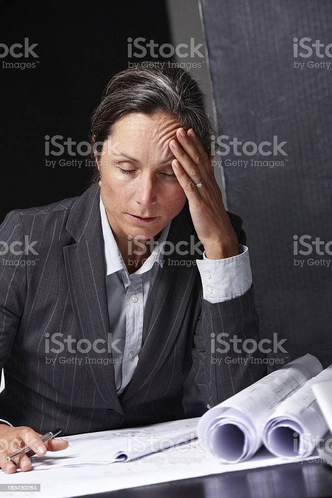 Exhausted female designer working on construction plans royalty-free stock photo