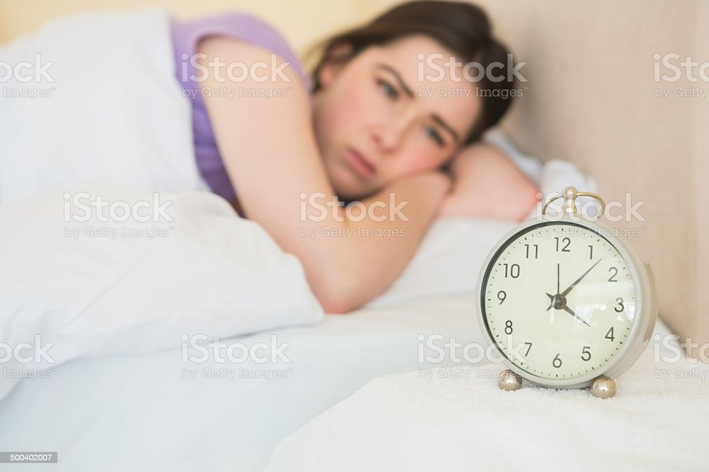 Exhausted girl waking up in her bed stock photo