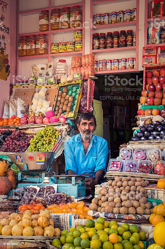 Exhausted greengrocer sitting in his shop stock photo