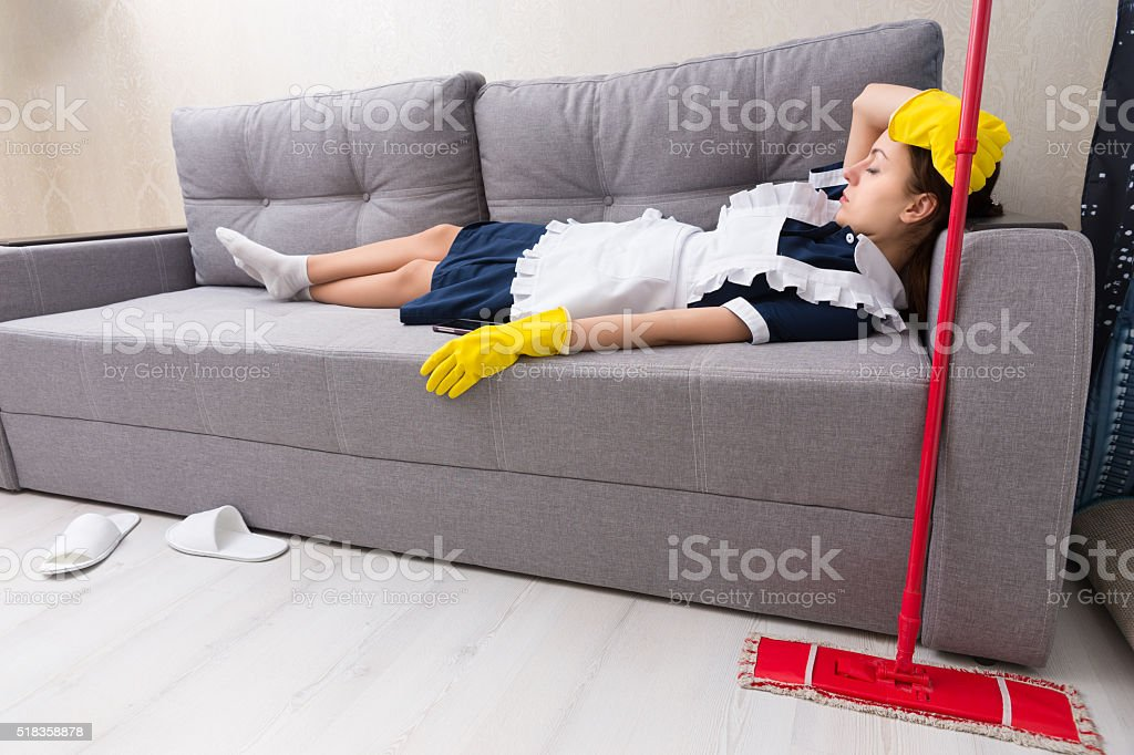 Exhausted housekeeper relaxing on the job stock photo