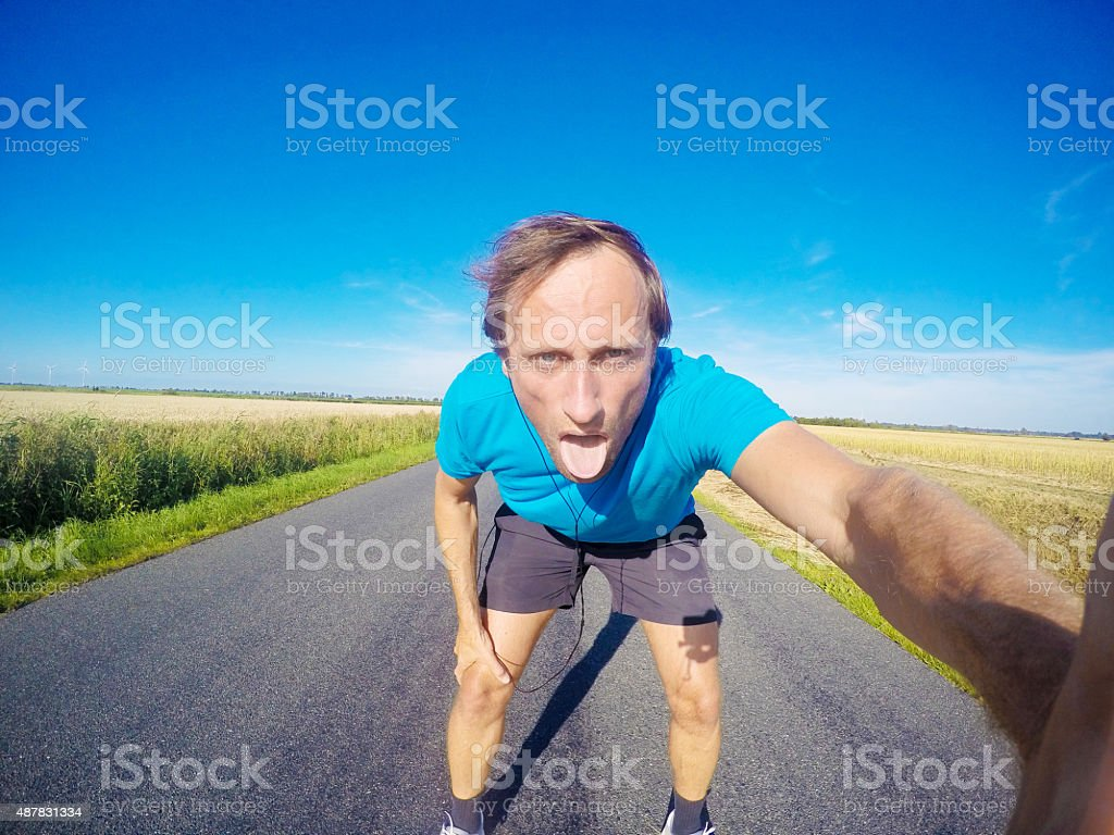 Exhausted jogger on tarr road, GoPro image stock photo