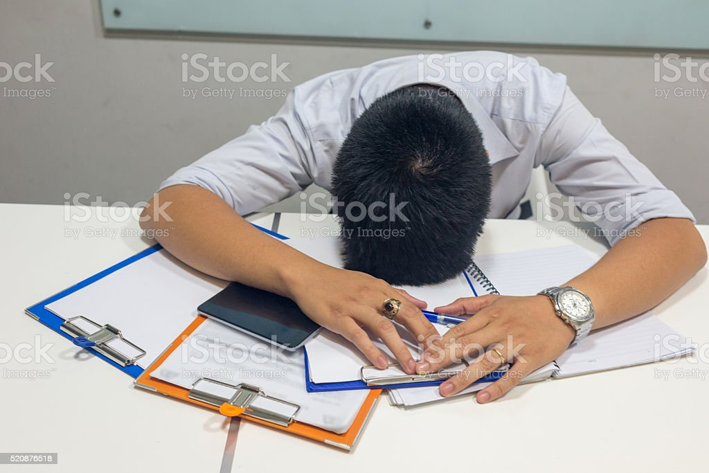 Exhausted man feeling stucked with report he dealing with stock photo