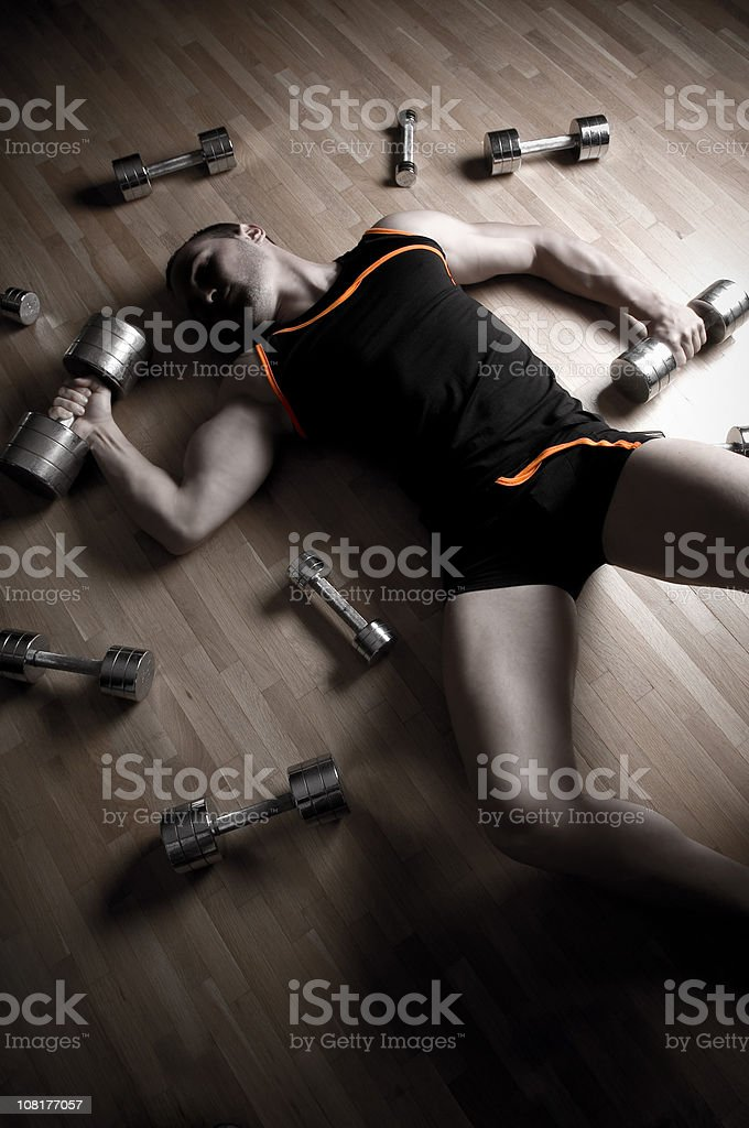 Exhausted Man Lies on Floor Surrounded by Barbells and Weights royalty-free stock photo