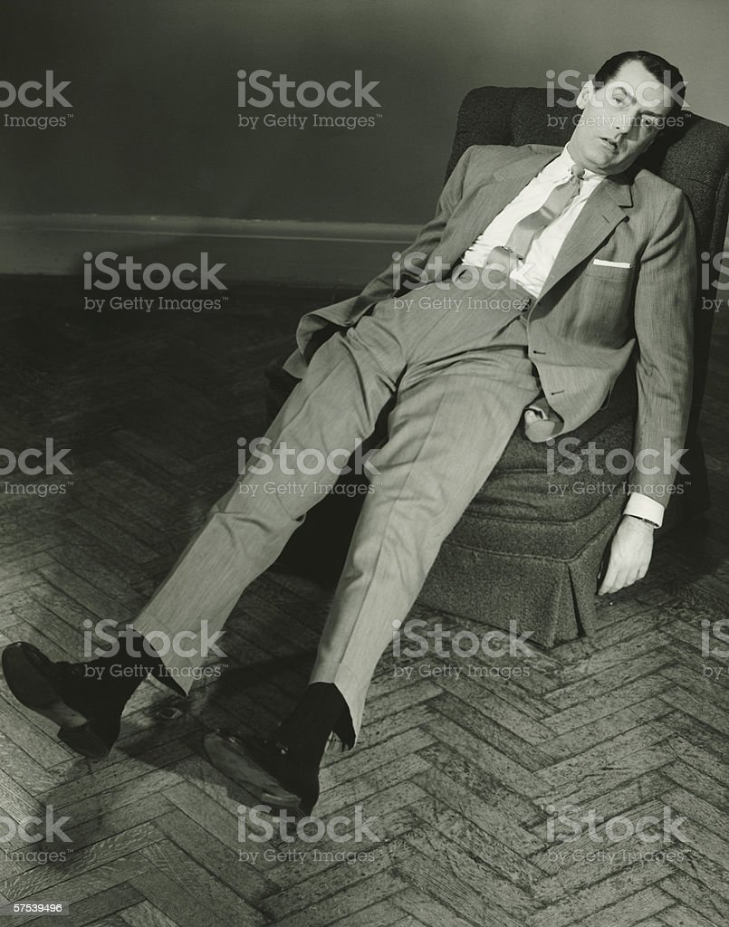 Exhausted man reclining on chair, (B&W), elevated view royalty-free stock photo