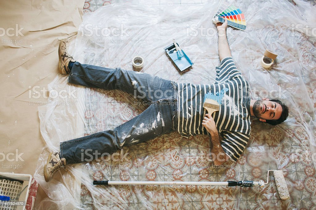 Exhausted man resting after hard painting work stock photo