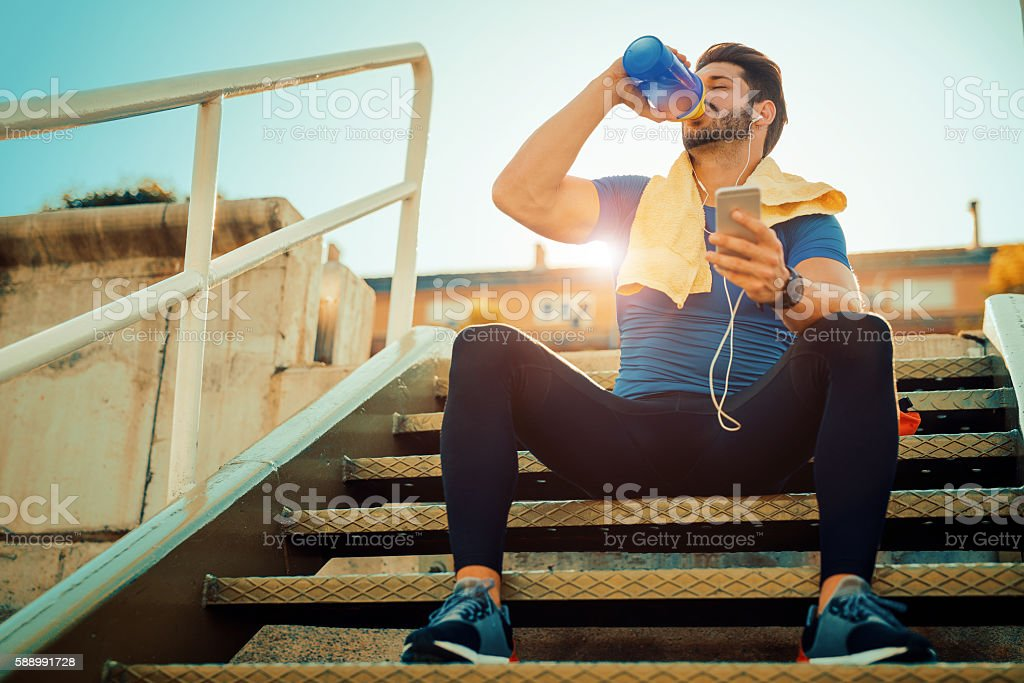 Exhausted man resting after jogging stock photo