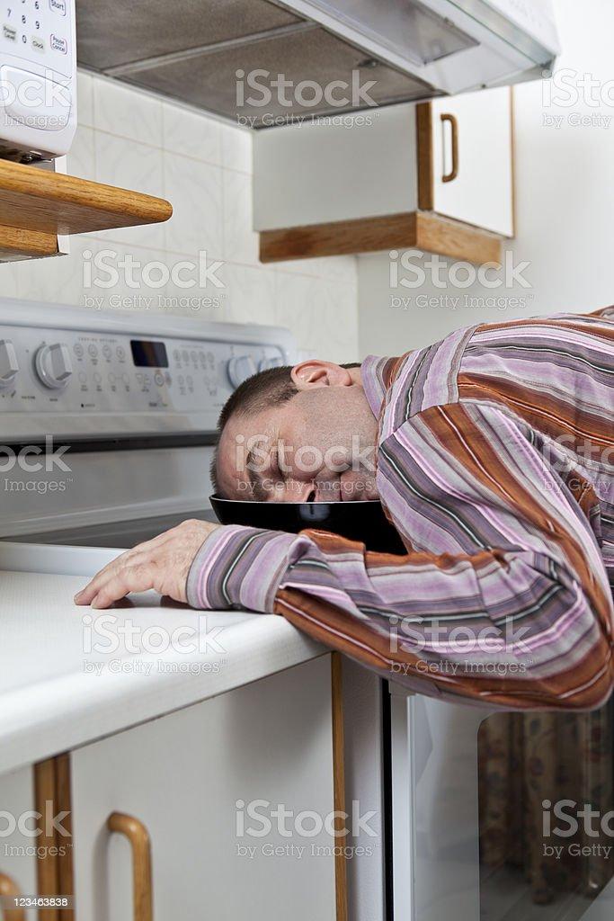 Exhausted man sleeping on stove top stock photo
