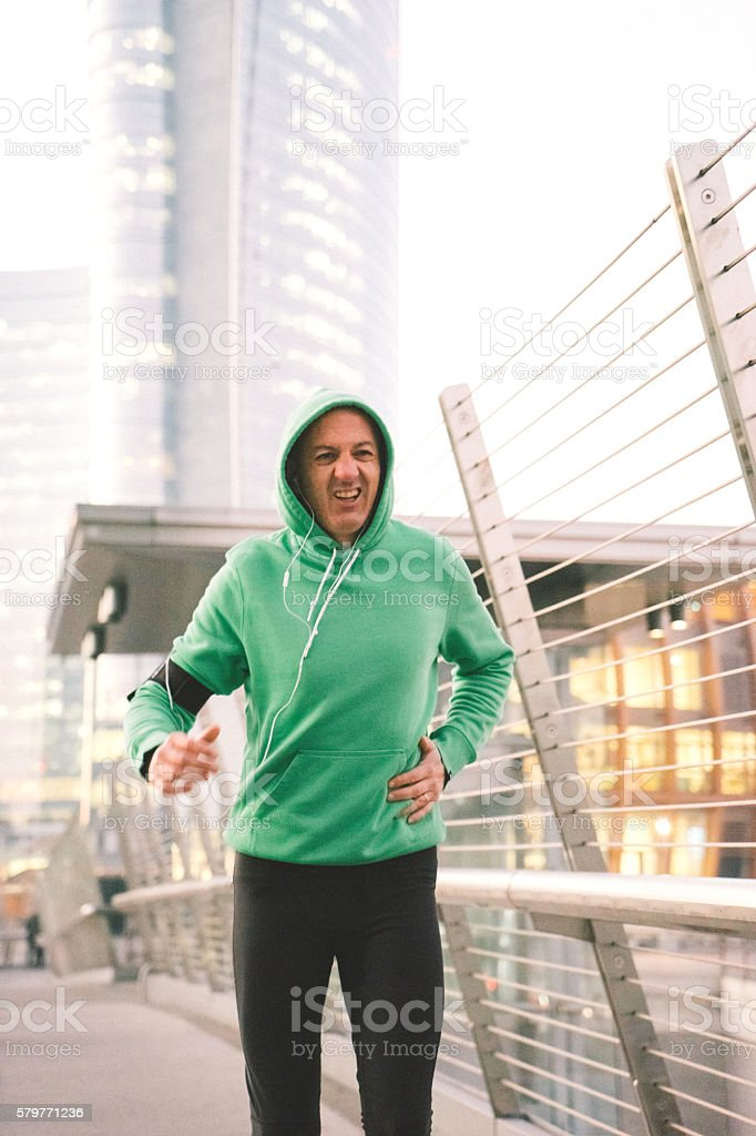 Exhausted Mature Male Runner, Cityscape On Background stock photo