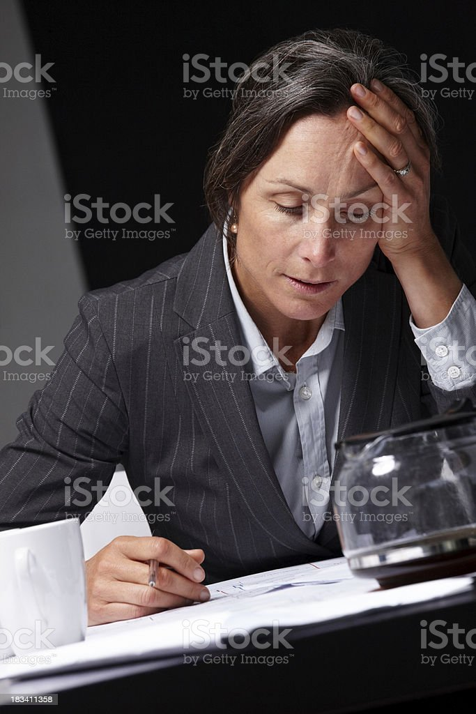 Exhausted mature woman working overtime in office royalty-free stock photo