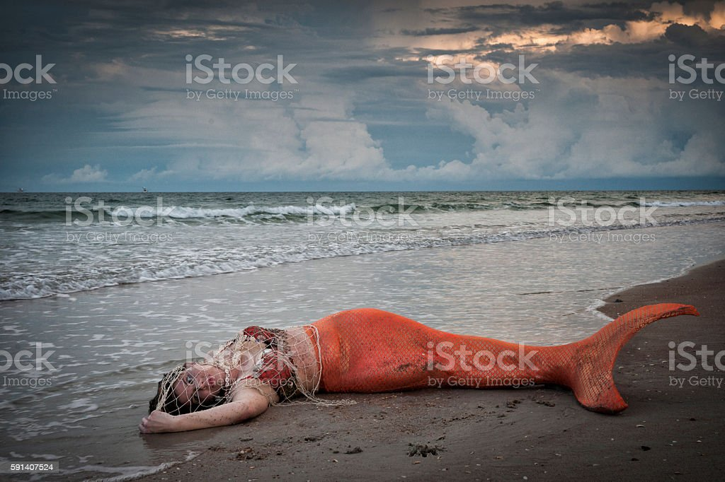 Exhausted mermaid lies on shore at Atlantic Ocean stock photo