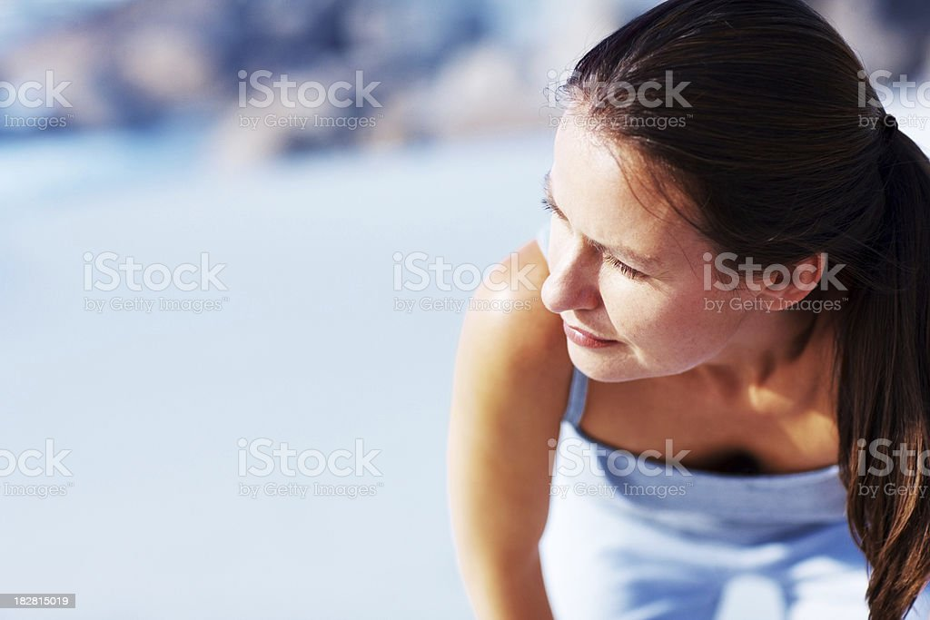 Exhausted mid adult woman bending over on the beach royalty-free stock photo