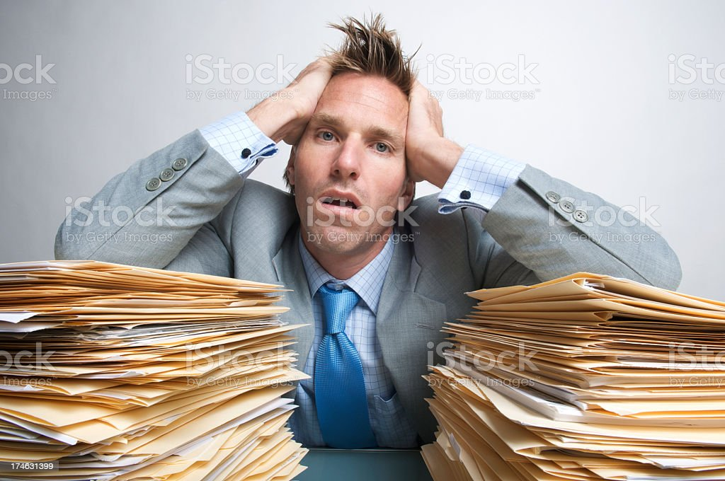Exhausted Office Worker Businessman Holding Head in Hands on Folders royalty-free stock photo
