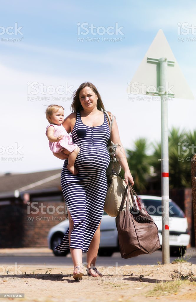 Exhausted overburdened pregnant woman carrying toddler and shopping bags stock photo