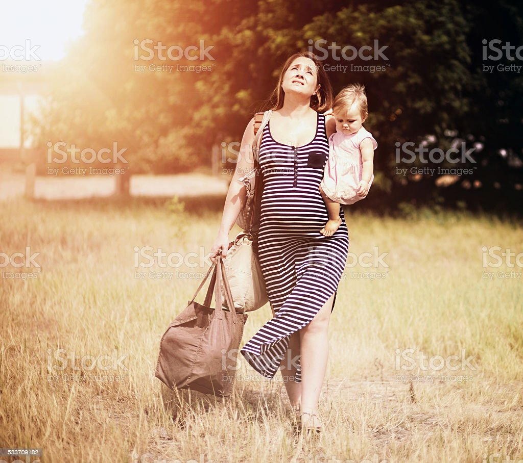 Exhausted pregnant woman with toddler trudging through hot sun stock photo