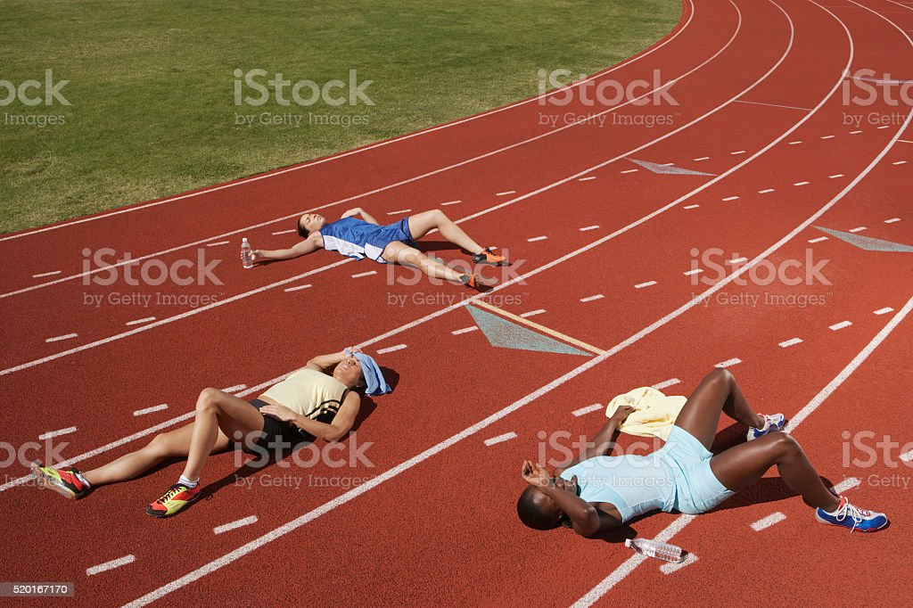 Exhausted runners on track stock photo