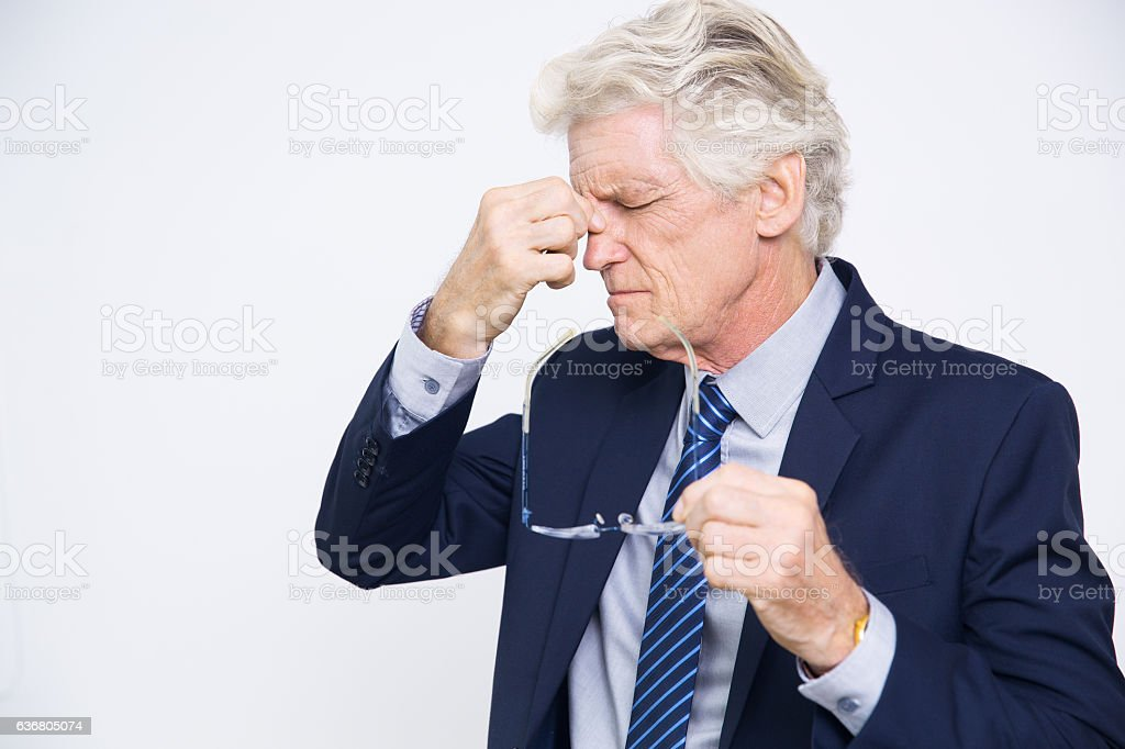 Exhausted senior man suffering from headache stock photo