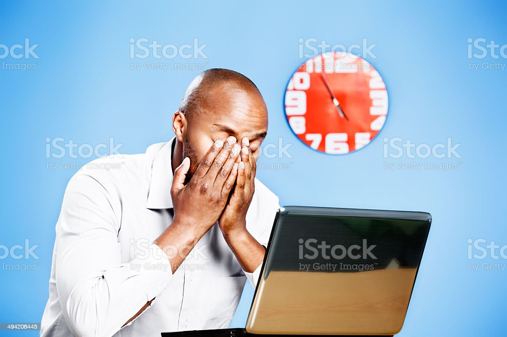 Exhausted, sleepy man with laptop, clock in background stock photo