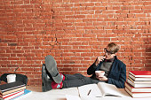 Exhausted student having snack at desk, free space
