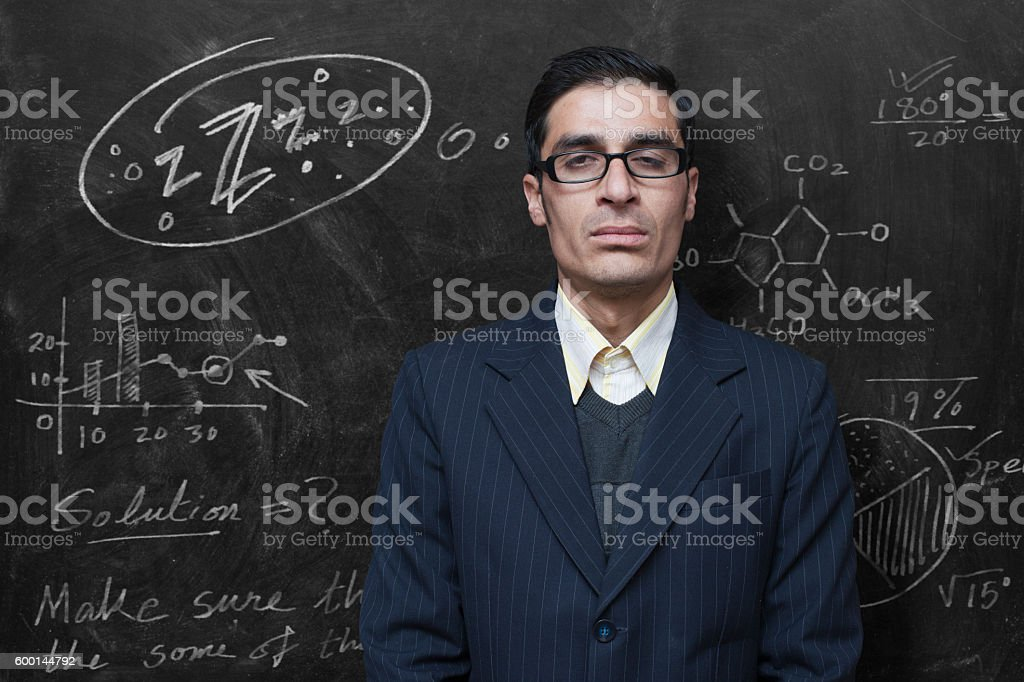 Exhausted teacher feeling sleepy in classroom standing against blackboard. stock photo