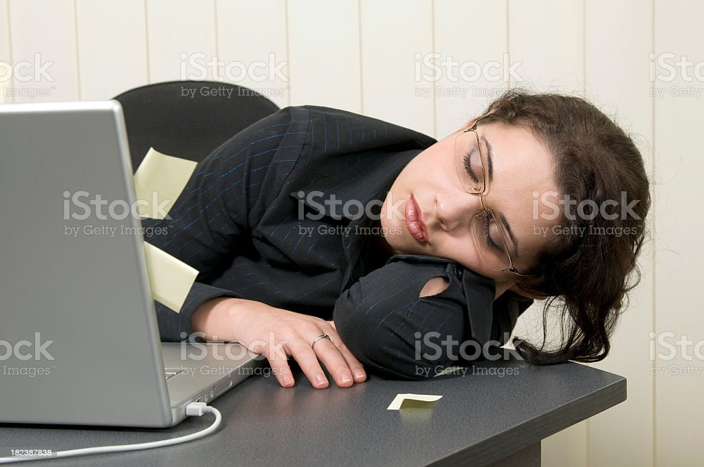 Exhausted woman asleep on the desk royalty-free stock photo