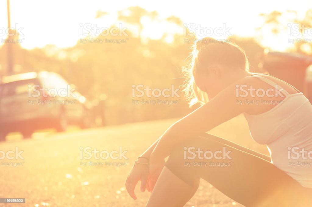 Exhausted woman sitting beside the road. stock photo