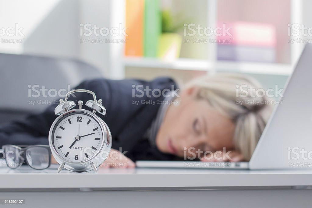 Exhausted woman sleeping in front of computer stock photo