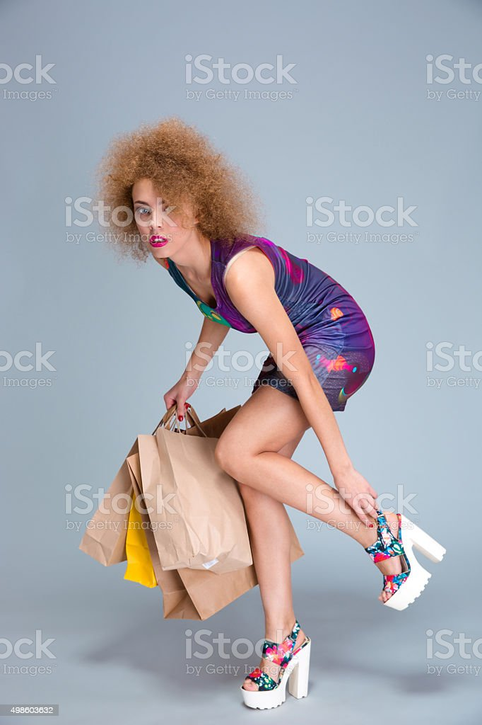 Exhausted woman touching her hurting legs on shopping stock photo